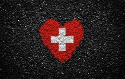 Bandera de Suiza, bandera suiza, corazón en el fondo negro, piedras, grava y tabla, pared texturizada fotos de archivo libres de regalías