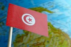 Bandera de Túnez con un mapa del globo como fondo Foto de archivo