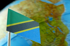 Bandera de Tanzania con un mapa del globo como fondo Foto de archivo libre de regalías