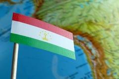 Bandera de Tayikistán con un mapa del globo como fondo Imágenes de archivo libres de regalías