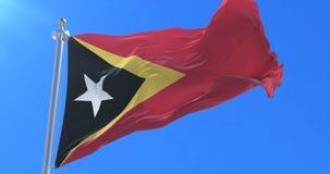 Bandera de Timor del Este que agita en el viento con el cielo azul en lento, lazo