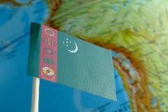 Bandera de Turkmenistán con un mapa del globo como fondo Imagen de archivo