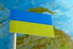 Bandera de Ucrania con un mapa del globo como fondo Imagenes de archivo