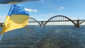 Bandera de Ucrania en el fondo del yate del río Dnieper y del puente sobre el río metrajes