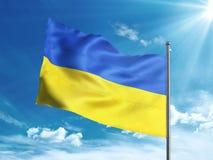 Bandera de Ucrania que agita en el cielo azul Foto de archivo