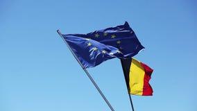 Bandera de unión europea y bandera belga que agita en el viento almacen de metraje de vídeo