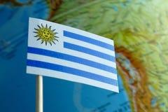 Bandera de Uruguay con un mapa del globo como fondo Fotografía de archivo