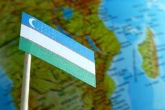 Bandera de Uzbekistán con un mapa del globo como fondo Fotos de archivo libres de regalías