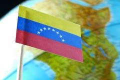Bandera de Venezuela con un mapa del globo como fondo Fotos de archivo