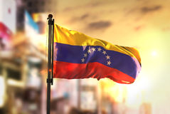 Bandera de Venezuela contra fondo borroso ciudad en la salida del sol Backli fotos de archivo libres de regalías