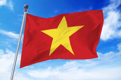 Bandera de Vietnam que se convierte contra un cielo azul foto de archivo