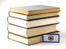 Bandera de Virginia Occidental con la pila de libros aislados en el backgrou blanco imágenes de archivo libres de regalías