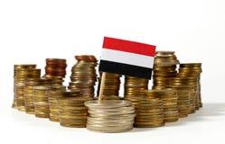 Bandera de Yemen con la pila de monedas del dinero Foto de archivo