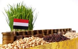 Bandera de Yemen que agita con la pila de monedas del dinero y las pilas de trigo Imagen de archivo libre de regalías