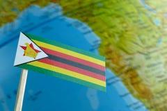 Bandera de Zimbabwe con un mapa del globo como fondo Imagen de archivo libre de regalías