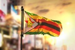 Bandera de Zimbabwe contra fondo borroso ciudad en la salida del sol Backlig Fotos de archivo