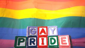 Bandera del arco iris que se mueve en la brisa con los bloques del orgullo gay en frente almacen de metraje de vídeo