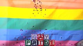 Bandera del arco iris que sopla en la brisa con los bloques del orgullo gay y caer del confeti almacen de video