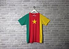 Bandera del Camerún en la camisa y colgante en la pared con el papel pintado del modelo del ladrillo