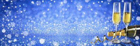 Bandera del champán de la tostada del Año Nuevo, fondo azul Fotografía de archivo libre de regalías