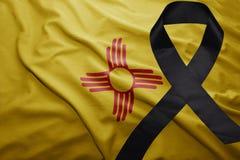 Bandera del estado de New México con la cinta de luto negra foto de archivo libre de regalías