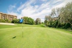 Bandera del golf en agujero en el campo de golf imagenes de archivo