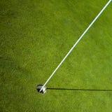 Bandera del golf en agujero verde Imagenes de archivo
