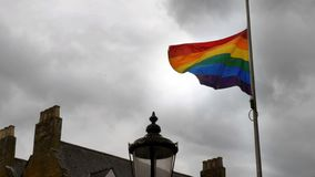 Bandera del orgullo del arco iris de LGBT que agita en el viento en fondo británico nublado del cielo en Northampton Inglaterra foto de archivo libre de regalías