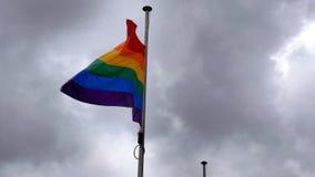 Bandera del orgullo del arco iris de LGBT que agita en el viento en fondo británico nublado del cielo en Northampton Inglaterra imagenes de archivo