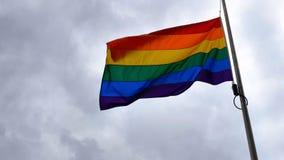Bandera del orgullo del arco iris de LGBT que agita en el viento en fondo británico nublado del cielo en Northampton Inglaterra foto de archivo