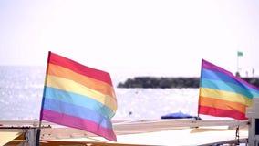 Bandera del orgullo gay de la cámara lenta que sopla en el viento en la playa de Sitges, España metrajes