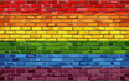 Bandera del orgullo gay en una pared de ladrillo
