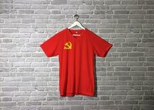 Bandera del Partido Comunista Chino en la camisa y colgante en la pared con el papel pintado del modelo del ladrillo fotografía de archivo
