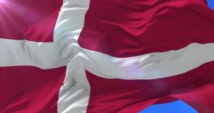 Bandera del Reino de Dinamarca que agita en el viento con el cielo azul, lazo