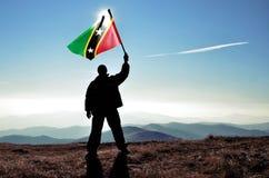 Bandera del santo San Cristobal y de Nevis de la silueta que agita del ganador acertado del hombre encima de la montaña foto de archivo