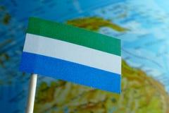 Bandera del Sierra Leone con un mapa del globo como fondo Imagenes de archivo