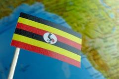Bandera del Ugandan con un mapa del globo como fondo Imagenes de archivo