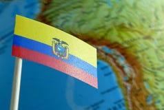 Bandera ecuatoriana con un mapa del globo como fondo Fotografía de archivo libre de regalías