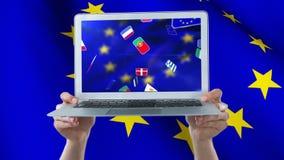 Bandera europea que agita en la pantalla del ordenador portátil almacen de metraje de vídeo