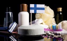 Bandera finlandesa en el jabón con todos los productos para la gente Imagenes de archivo