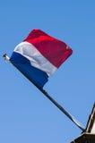 Bandera francesa contra el cielo nublado azul Foto de archivo libre de regalías