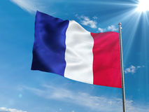 Bandera francesa que agita en cielo azul con el sol Imagen de archivo