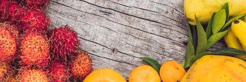 BANDERA, frutas coloridas en la tabla de madera blanca, plátanos, carambola, mango, papaya, mandarín, rambutan, Pamela, copia del Fotografía de archivo