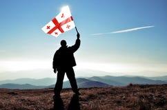 Bandera georgiana que agita de la silueta del ganador acertado del hombre encima de la montaña foto de archivo libre de regalías