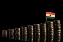Bandera ghanesa con la porción de monedas aisladas en negro fotografía de archivo