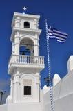 Bandera griega al lado de la torre de iglesia, santorin Fotos de archivo