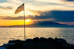 Bandera griega, costa, puesta del sol Imagen de archivo libre de regalías