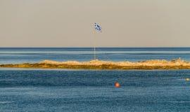Bandera griega en pequeño trozo de tierra en el mar Fotografía de archivo libre de regalías