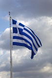 Bandera griega en una asta de bandera contra las nubes oscuras imagen de archivo