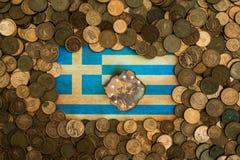 Bandera griega rodeada por las monedas euro imagen de archivo